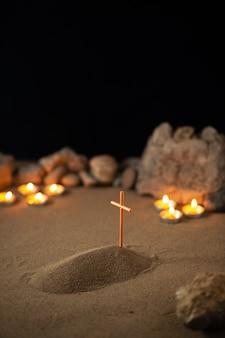 Des bougies allumées avec des pierres et une petite tombe sur une surface sombre de sable