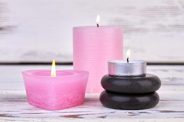 Bougies allumées et pierres polies noires pour spa
