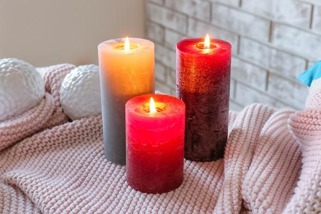 Des bougies allumées sur un plaid dans la chambre