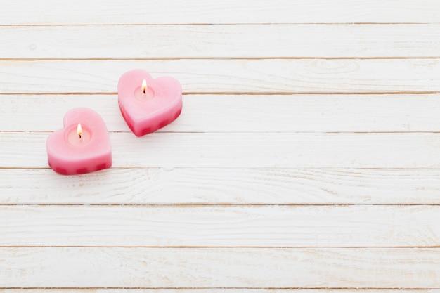 Bougies allumées roses sur bois blanc