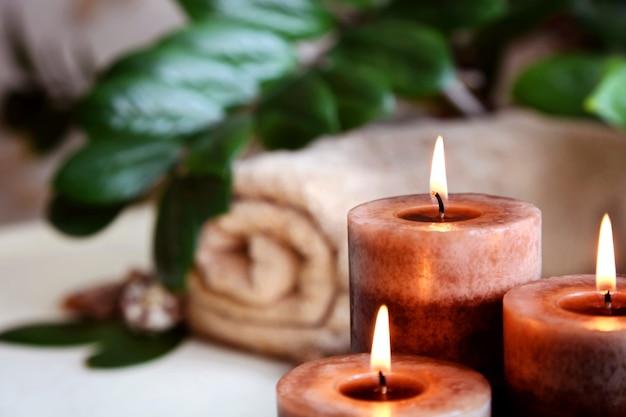 Des bougies allumées et une serviette. thérapie de pierre. traitements spa.