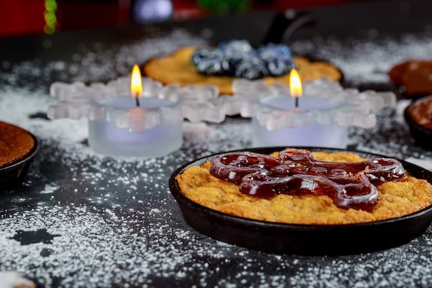 Des bougies allumées sur la table à manger avec de la nourriture, décorées pour la nuit de noël