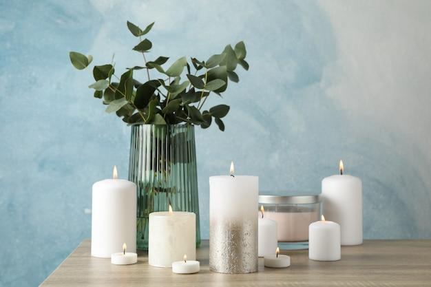 Bougies allumées et vase avec eucalyptus sur table en bois sur bleu