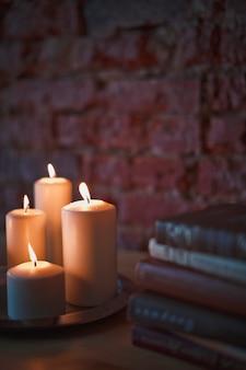 Des bougies allumées et de vieux livres sur la table dans une pièce sombre.