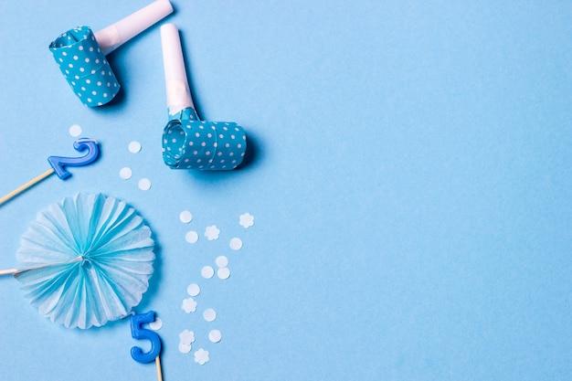 Bougies d'anniversaire confettis et pailles sur bleu
