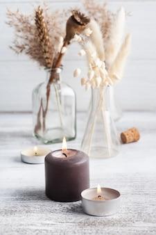 Bougies aromatiques allumées et fleurs sèches sur table rustique. arrangement de spa dans un style monochrome