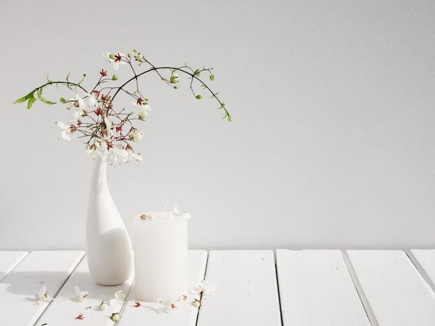 Bougies blanches et belles fleurs de nodding clerodendr dans une composition de vase en verre moderne sur l'intérieur de la salle de table en bois blanc, nature morte d'été