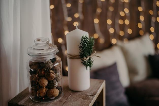 Bougies blanches avec des branches de sapin et un pot de noix
