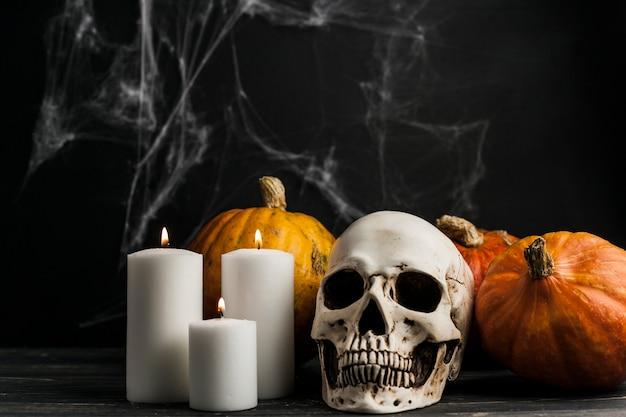 Bougies blanches avec le crâne et les citrouilles