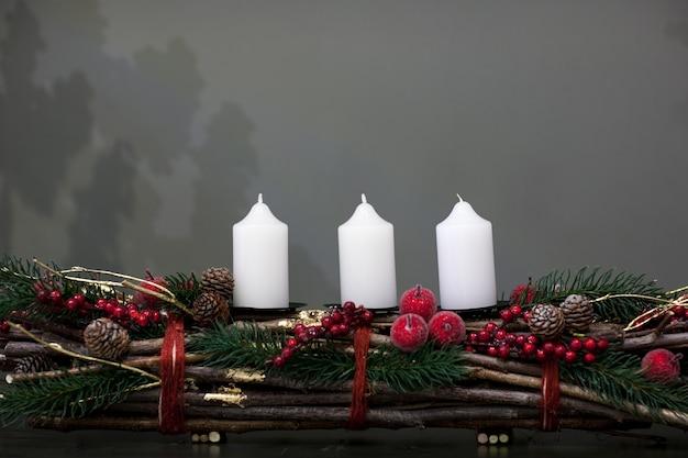 Bougies blanches de noël sur un tas de brindilles décorées de pommes de sapin et de baies