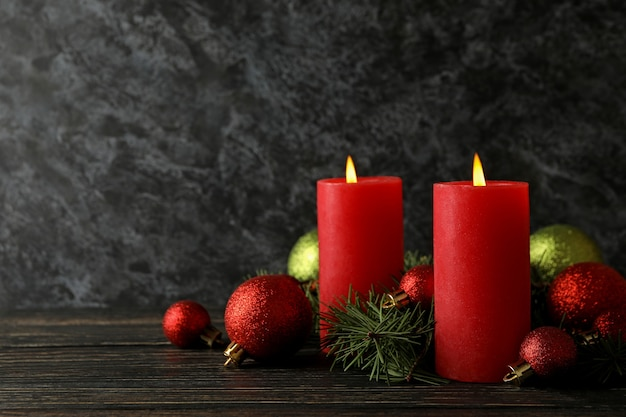 Bougies, boules et branches de pin sur fond de bois