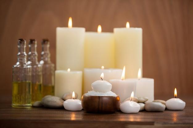 Bougies avec des bouteilles d'huile de massage et de sel de mer dans un bol en bois