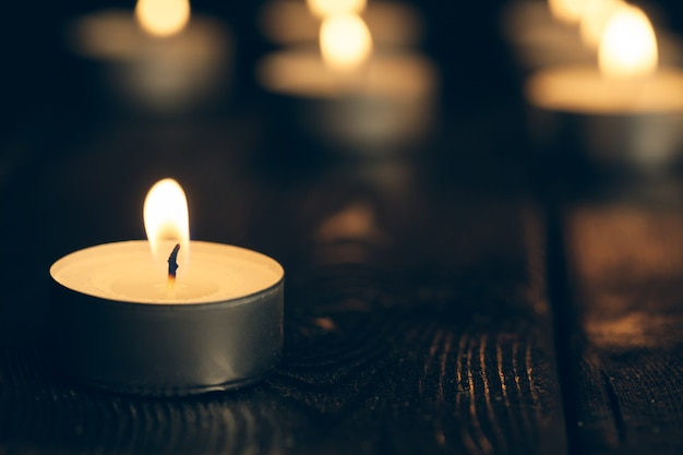 Des bougies brûlent dans l'obscurité sur le noir. concept de commémoration.