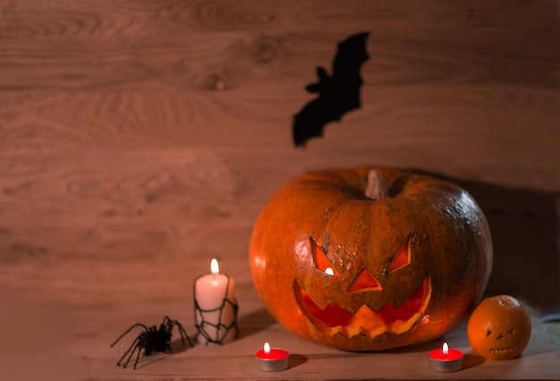 Bougies, citrouilles et une araignée sur un fond en bois .photo with copy space