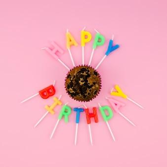 Des bougies colorées autour d'un délicieux muffin