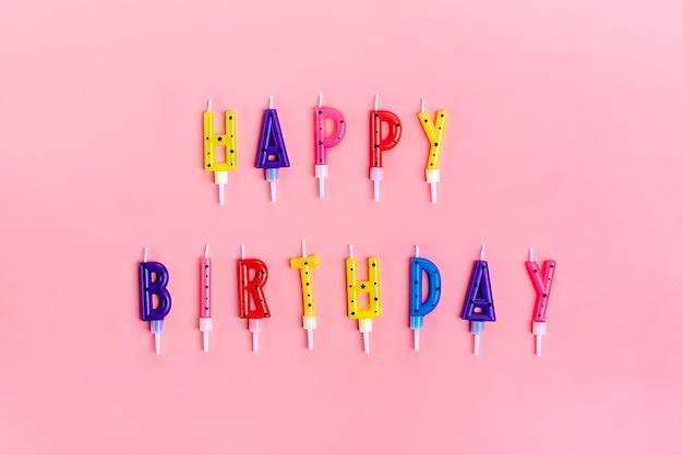 Bougies colorées sur le gâteau sous forme de lettres joyeux anniversaire rose