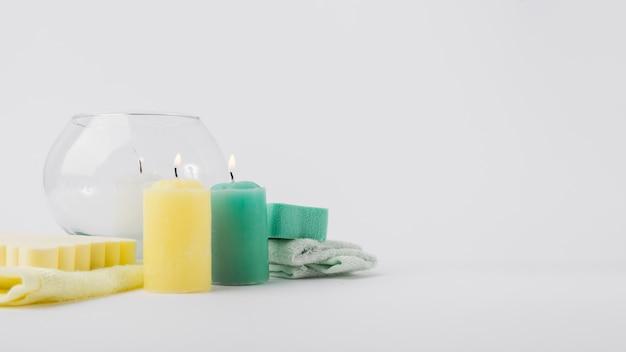 Bougies colorées lumineuses avec éponge et serviette isolé sur fond blanc
