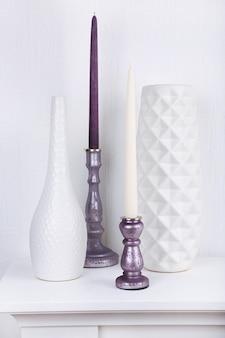 Bougies dans des bougeoirs et des vases sur table sur blanc