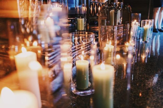 Des bougies dans de grands vases se tiennent sur le sol