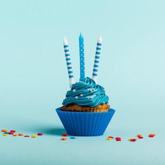 Bougies décoratives sur les muffins avec étoile saupoudrent contre