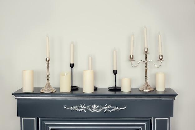 Bougies de différents types et tailles sur le comptoir de cheminée d'imitation près du mur