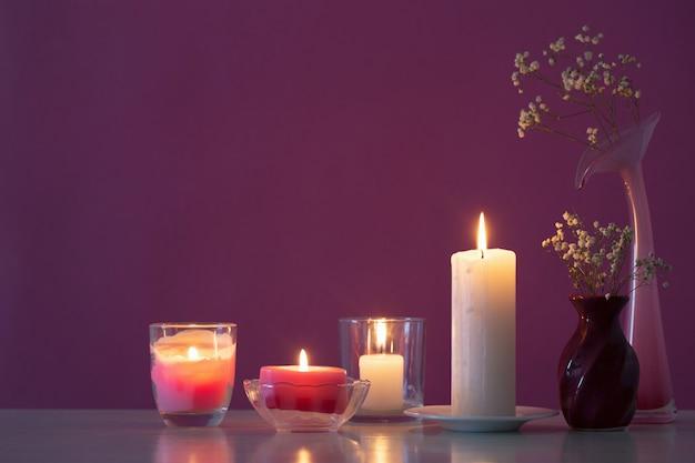 Bougies avec des fleurs sur une table en bois blanc sur fond violet