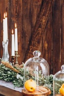 Bougies hautes blanches en chandeliers de cristal, bougies sur fond texturé en bois rustique vieilli.
