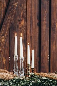 Bougies hautes blanches en chandeliers de cristal sur fond texturé en bois rustique.
