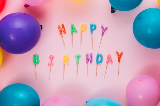 Bougies joyeux anniversaire avec des ballons colorés sur fond rose