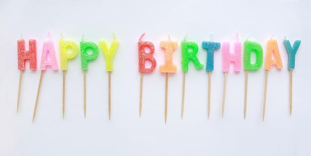 Bougies joyeux anniversaire multicolores sur fond blanc