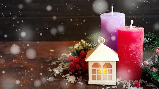 Bougies, lanterne de maison et décoration de noël sur fond en bois foncé