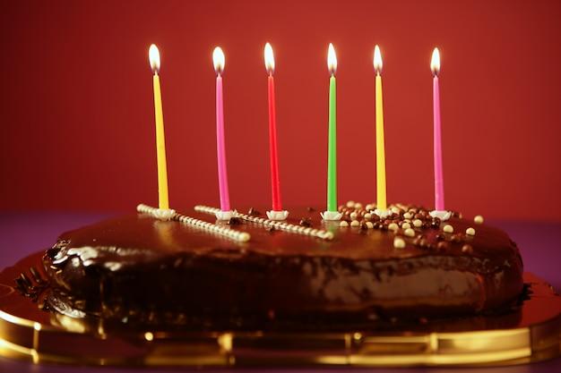 Bougies lumineuses d'anniversaire colorées dans un gâteau au chocolat