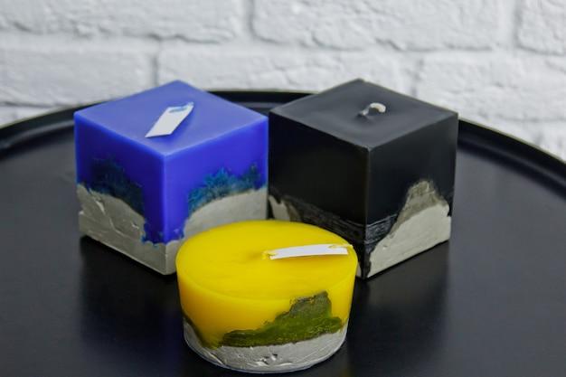 Bougies multicolores faites maison avec du béton sur la surface d'un mur blanc
