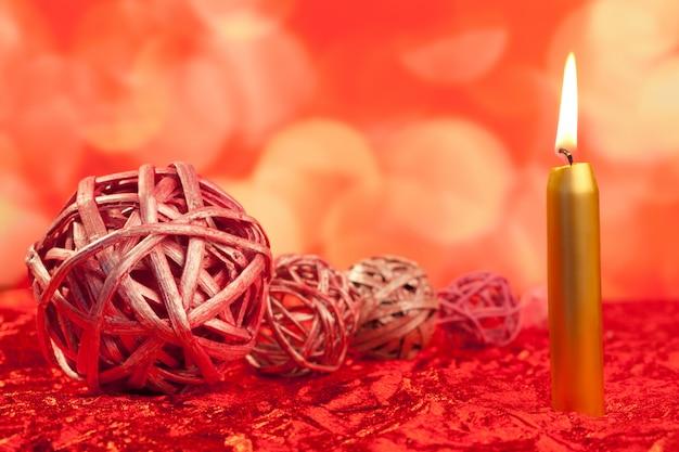 Bougies de noël avec des boules séchées sur rouge