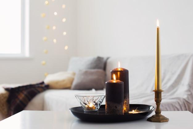 Bougies noires et dorées sur table blanche