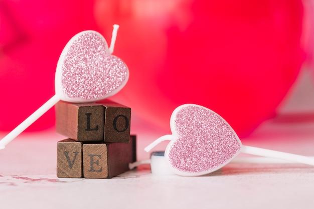 Bougies d'ornement du symbole du coeur près du titre d'amour des baguettes en bois