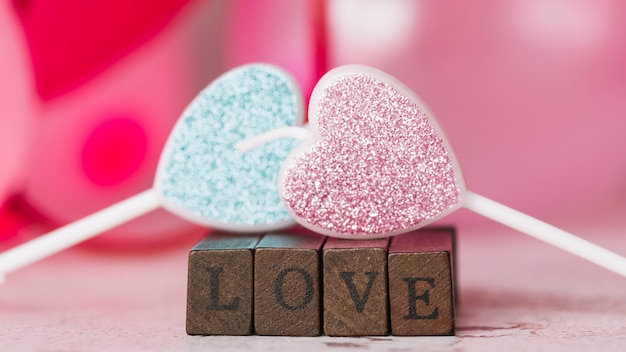 Bougies d'ornement en forme de coeur près du titre d'amour de baguettes en bois
