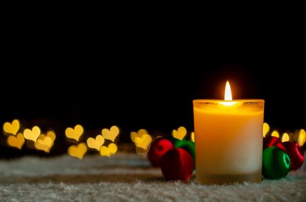 Bougies et ornements de noël avec des lumières bokeh en forme d'amour.