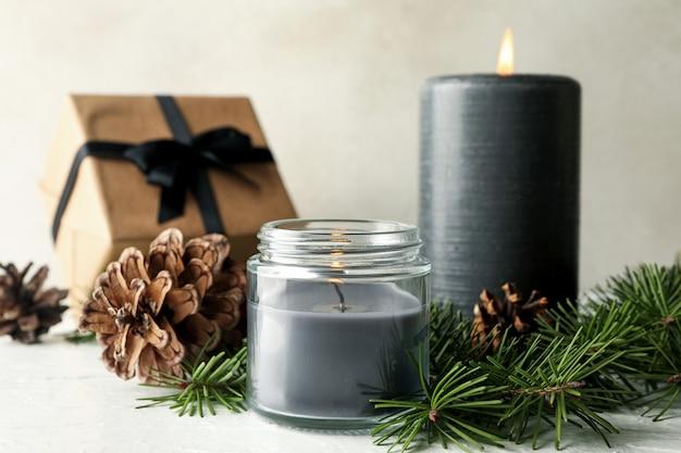 Bougies parfumées, boîte-cadeau et branches de pin avec des cônes sur tableau blanc