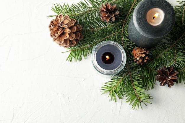 Bougies parfumées et branches de pin avec des cônes sur tableau blanc
