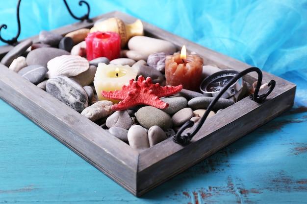 Bougies sur plateau vintage avec galets de mer, étoiles de mer et coquillages sur fond de bois
