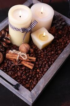 Bougies sur plateau vintage avec grains de café et épices, bosses sur table en bois, sur surface sombre