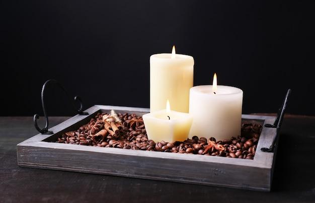 Bougies sur plateau vintage avec grains de café et épices sur table en bois