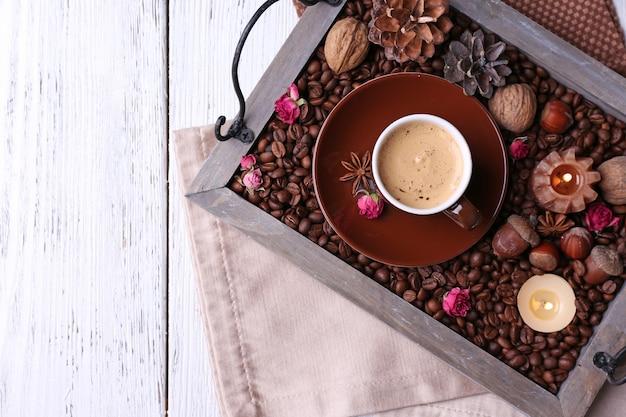 Bougies sur plateau vintage avec grains de café et épices, tasse de thé sur fond de bois de couleur
