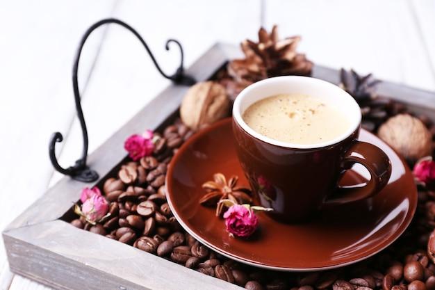 Bougies sur plateau vintage avec grains de café et épices, tasse de thé sur une surface en bois de couleur