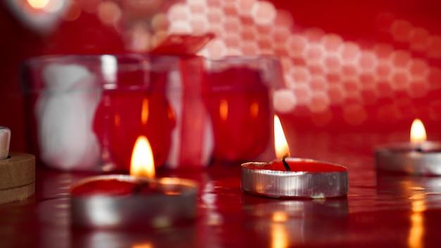 Bougies pour la saint-valentin, table avec fond rouge festif.