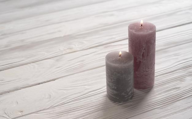 Bougies roses et grises sur une table en bois blanche
