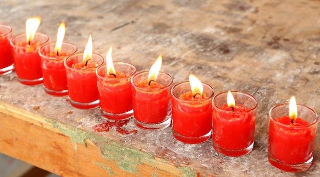 Bougies rouges alignées brûlant dans le verre