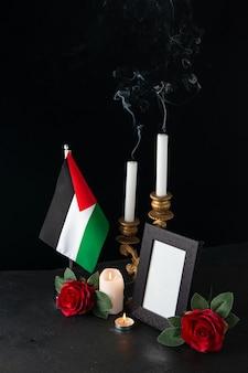 Bougies sans feu avec drapeau palestinien et fleurs sur une surface sombre