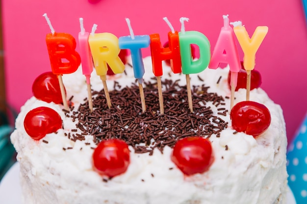 Bougies de texte d'anniversaire coloré sur un gâteau blanc